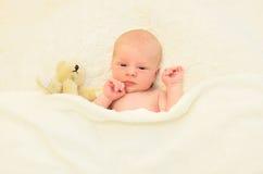 Bebê bonito que dorme junto com o brinquedo do urso de peluche na casa da cama Imagens de Stock Royalty Free