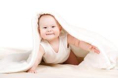 Bebê bonito que espreita para fora de debaixo da cobertura Fotografia de Stock Royalty Free