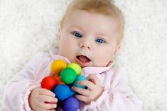 Beb? bonito que joga com o brinquedo de madeira colorido do chocalho imagem de stock