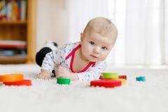 Beb? bonito que joga com o brinquedo de madeira colorido do chocalho imagens de stock