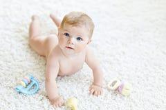 Beb? bonito que joga com o brinquedo pastel colorido do chocalho do vintage Crian?a rec?m-nascida, menina que olha a c?mera e imagem de stock