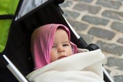 Bebê com hoodie cor-de-rosa em um carrinho de criança que olha a câmera Fotografia de Stock