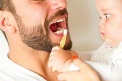 Bebê com os dentes de escovadela da escova de dentes do pai Fotografia de Stock Royalty Free