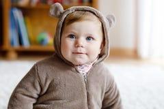Beb? com os olhos azuis que vestem o inverno do urso marrom overal no quarto ensolarado Crian?a rec?m-nascida que est? sendo vest foto de stock royalty free
