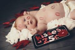 Bebé con besos del lápiz labial por todo él Fotos de archivo