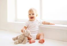Bebé con el juguete del oso de peluche que se sienta a casa en el sitio blanco cerca del viento Imagen de archivo