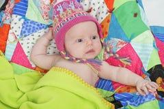 Bebé con el sombrero y el edredón coloridos Imagenes de archivo