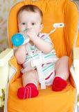 Bebé con la alimentar-botella que se sienta en el highchair Imagen de archivo