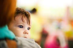 Bebé curioso que parece enfocado Imagen de archivo
