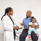 Bebê da terra arrendada do pai que fala ao pediatra. Imagem de Stock Royalty Free