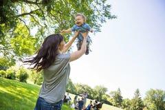 Bebé de elevación de la madre joven juguetona en el parque Imagen de archivo
