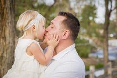 Bebé de Kisses His Cute del padre afuera en el parque Fotos de archivo libres de regalías
