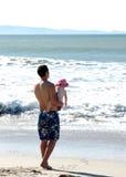 Bebé de la explotación agrícola del padre en la playa Fotografía de archivo