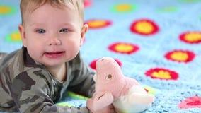 Beb? de sorriso bonito: Um beb? pequeno lindo encontra-se na cama e nos sorrisos na c?mera com um foco macio agrad?vel video estoque