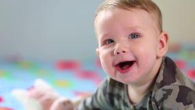 Beb? de sorriso bonito: Um beb? pequeno lindo encontra-se na cama e nos sorrisos na c?mera com um foco macio agrad?vel filme