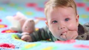 Beb? de sorriso bonito: Um beb? pequeno lindo encontra-se na cama e nos sorrisos na c?mera com um foco macio agrad?vel vídeos de arquivo