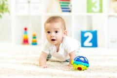 Bebé divertido de arrastre en el cuarto de niños Foto de archivo libre de regalías