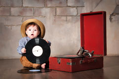 Bebé divertido en sombrero retro con el disco de vinilo y el gramófono Imagen de archivo