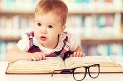 Bebé divertido en vidrios que lee un libro en biblioteca Fotos de archivo libres de regalías