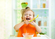Bebé divertido que come la comida sana en cocina Foto de archivo