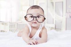 Bebé dulce con los vidrios en dormitorio Foto de archivo