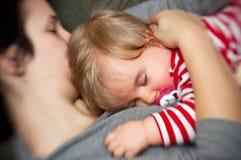 Bebé durmiente del asimiento de la madre Fotografía de archivo