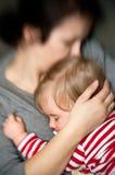Bebé durmiente del asimiento de la madre Fotos de archivo