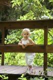 Bebê em uma ponte de madeira Fotografia de Stock Royalty Free
