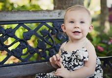 Bebé en banco de parque Foto de archivo