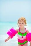 Bebé en brazal inflable que camina en la playa Imagen de archivo