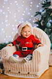 Bebé en el traje de Santa Claus que se sienta debajo del árbol de navidad Imagenes de archivo