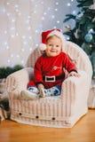 Bebé en el traje de Santa Claus que se sienta debajo del árbol de navidad Imagen de archivo libre de regalías