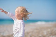 Bebé en la playa que mira en distancia Imagenes de archivo