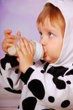 Bebé en leche de consumo del traje de la vaca de la botella Imágenes de archivo libres de regalías