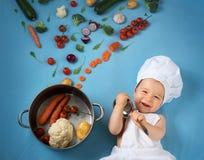 Bebé en sombrero del cocinero con cocinar la cacerola y verduras Foto de archivo libre de regalías