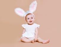 Bebé encantador que se sienta en el conejito de pascua del traje Fotografía de archivo