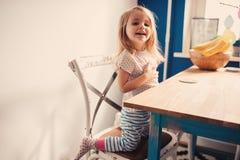 Bebê feliz bonito que tem o divertimento na cozinha Foto de Stock