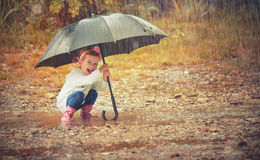 Bebé feliz con un paraguas en la lluvia que juega en la naturaleza Imagen de archivo