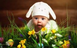 Bebé feliz del niño vestido como el conejo de conejito de pascua en la hierba Imagen de archivo