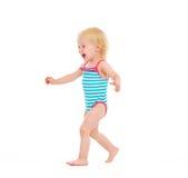 Bebé feliz en el traje de baño que se ejecuta en blanco Foto de archivo