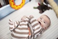 Bebé feliz en pesebre Imagen de archivo