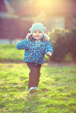 Bebé feliz que corre el parque iluminado por el sol de la primavera Imagen de archivo