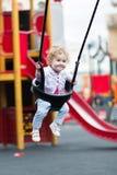 Bebé feliz que disfruta de un paseo del oscilación en un patio Imágenes de archivo libres de regalías
