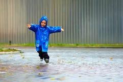 Bebé feliz que funciona con la calle, tiempo lluvioso Fotografía de archivo