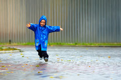 Bebé feliz que funciona a rua, tempo chuvoso Fotografia de Stock