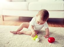 Beb? feliz que joga com as bolas no assoalho em casa foto de stock