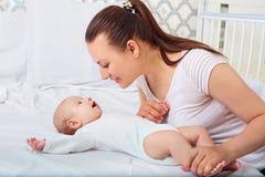 Bebé feliz que miente cerca de su madre en una cama blanca Mirada de las muchachas Imagen de archivo
