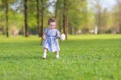 Bebé hermoso con la flor blanca grande del aster Imagenes de archivo
