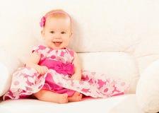 Bebé hermoso en un vestido rosado que se sienta en el sofá en casa Imagen de archivo