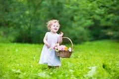 Bebé hermoso que camina con una cesta de la flor Imagenes de archivo